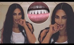 Kim Kardashian shows off her 'new grillz' as she encrusts her teeth in diamonds and a tiny cross